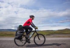 在路的愉快的骑自行车的人乘驾在冰岛 旅行和体育图片 库存照片