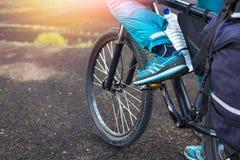 在路的愉快的骑自行车的人乘驾在冰岛 旅行和体育图片 免版税图库摄影