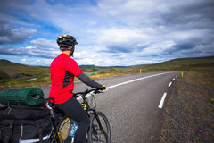 在路的愉快的骑自行车的人乘驾在冰岛 旅行和体育图片 免版税库存照片
