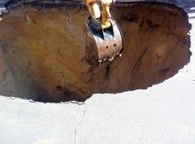 在路的挖掘机桶开掘的坑 免版税图库摄影