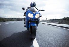 在路的摩托车司机 免版税库存照片