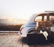 在路的汽车准备好在暑假在与行李的日落期间 免版税库存图片