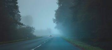 在路的汽车在一个有薄雾的秋天森林司机` s视图 库存图片