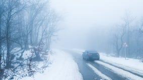 在路的汽车在有雾的多雪的森林里 图库摄影