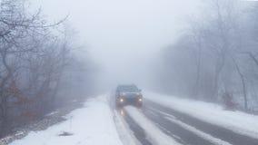 在路的汽车在有雾的多雪的森林里 库存图片