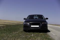 在路的汽车在领域附近 免版税图库摄影
