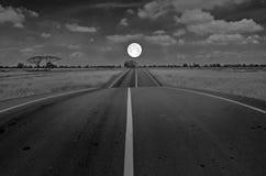在路的满月在领域 免版税库存照片