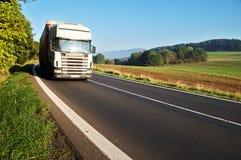 在路的白色卡车在一个农村风景 免版税库存照片