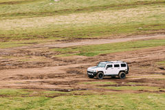 在路的白色发嗡嗡声的东西H2 SUV汽车在春天山大局 免版税库存图片