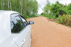 在路的白色汽车中止在土和石渣路 库存图片