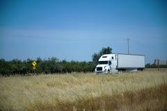 在路的白色现代半卡车有黄色干草的 图库摄影
