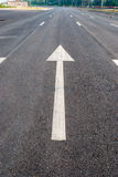 在路的白色箭头标志 免版税库存图片