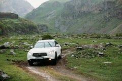 在路的白色Infiniti FX30d涡轮柴油SUV汽车在春天 免版税库存照片