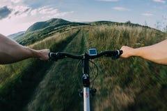 在路的自行车骑马 第一人景色 免版税库存图片