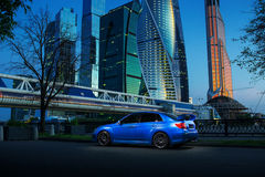 在路的蓝色汽车逗留在微明的莫斯科城市附近 免版税图库摄影