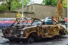 在路的被烧的汽车有在背景的汽车通行的 免版税库存图片