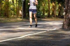 在路的运动员妇女连续锻炼在公园,健康概念 免版税库存图片