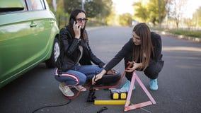 在路的问题 故障的汽车 电话技术协助 在一辆残破的汽车附近的两名妇女 股票录像