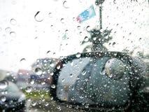 在路的雨天,在汽车镜子的雨珠有旁边后视镜的 免版税库存图片