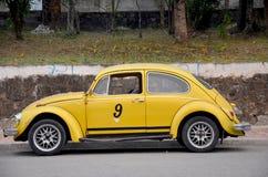 在路的经典减速火箭的黄色汽车大众甲壳虫 免版税图库摄影