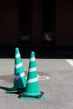 在路的绿色和白色交通锥体 免版税库存照片