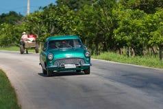 在路的绿色美国经典汽车驱动在乡下圣克拉拉古巴 库存照片
