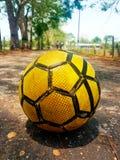 在路的黄色足球向幸福 免版税库存照片