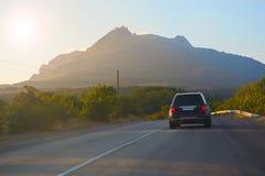在路的SUV在山 库存图片