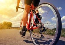 在路自行车的骑自行车者骑马 库存照片