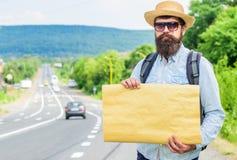 在路边缘的人有胡子的旅行者立场有白纸标志的,拷贝空间 使用标志的好处与名字 免版税库存照片