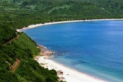 在路附近的偏僻的蓝色海洋海滩 免版税库存图片
