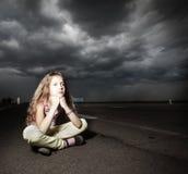 在路附近的哀伤的女孩 免版税图库摄影