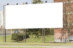 在路附近的大空白的广告牌有城市视图背景 免版税库存照片