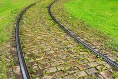 在路面和绿草的路轨 库存照片