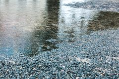 在路面的雨水水坑与波纹和天空反射 免版税图库摄影