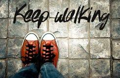 在路面的Keep走的词有鞋子背景,启发行情 图库摄影