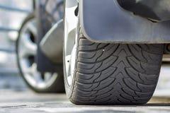 在路面背景停放的黑发光的豪华车胎的后面看法细节零件在明亮的好日子 运输, 库存照片