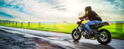在路骑马的摩托车 获得乘坐空的路的乐趣 库存图片