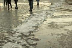 在路,解冻的雪融雪 步行者陷在雪,湿鞋子 早期的春天天气 免版税图库摄影