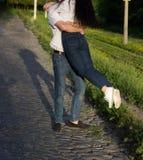 在跳舞和转动在牛仔裤和白色衬衫的爱的愉快的夫妇 免版税库存照片