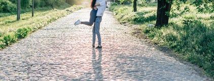 在跳舞和转动在牛仔裤和白色衬衫的爱的愉快的夫妇 免版税库存图片