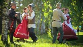 在跳舞在领域的传统俄国衣裳的两对夫妇由手风琴音乐 影视素材