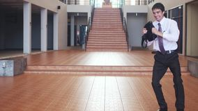 在跳舞现代的芭蕾舞剧的西装的一个年轻愉快的英俊的商人反对商业中心的背景 股票视频