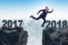 在跳跃从2017年到2018年的圣诞老人帽子的商人 免版税库存图片