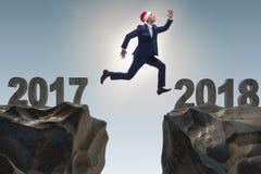 在跳跃从2017年到2018年的圣诞老人帽子的商人 库存照片