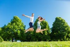在跳跃在公园的爱的夫妇 免版税库存图片
