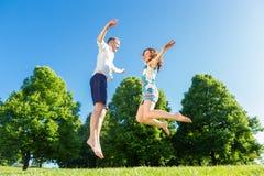 在跳跃在公园的爱的夫妇 库存照片
