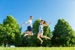 在跳跃在公园的爱的夫妇 库存图片