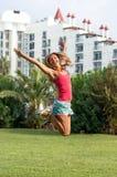 在跳跃在领域夏时绿草的桃红色T恤杉的年轻人微笑的美丽的卷曲金发微小的女孩时尚画象 库存照片