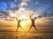 在跳跃的爱的夫妇在海滩在惊人的日落期间 幸福 免版税库存图片